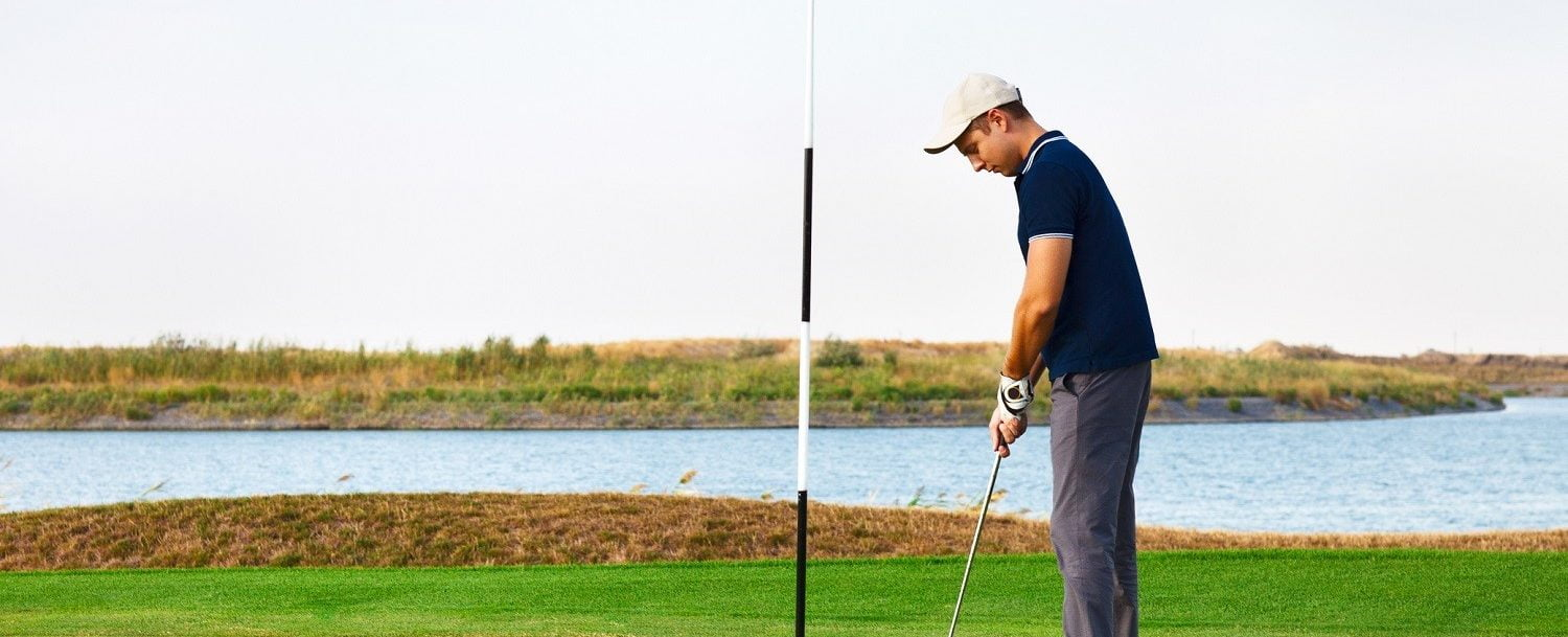 Athletic young man playing golf in golf club near the water