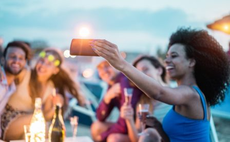 Happy friends taking selfie with smartphone at beach party outdoor - Young people having fun at kiosk bar drinking champagne - Soft focus on mobile cell phone - Youth lifestyle and vacation