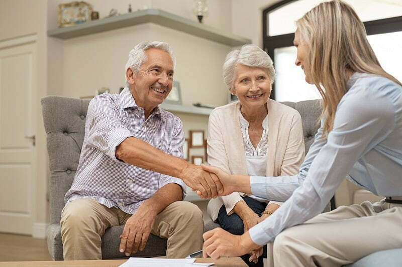 Senior couple shaking hands with financial advisor